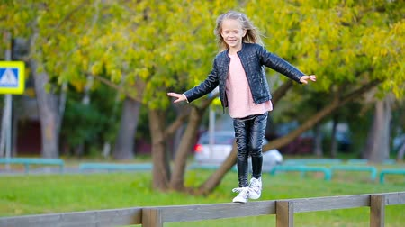 golden falls : Adorable little girl outdoors at beautiful autumn day Stock Footage