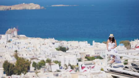 Киклады : Beautiful young woman reading book in luxury hotel with amazing view on Mykonos, Greece