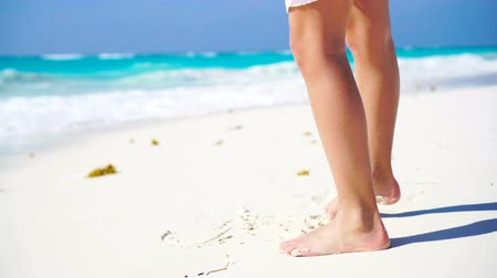 protects : Close-up legs walking along the white beach in shallow water. Concept of beach vacation and barefoot. No shoes no news