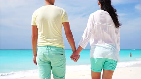 turkuaz : Young couple holding hands at tropical beach. Closeup SLOW MOTION