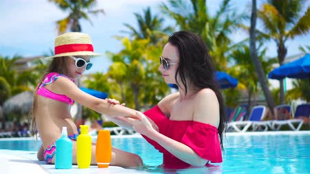 banhos de sol : Young mother applying sun cream to kid nose in swimming pool. The concept of protection from ultraviolet radiation