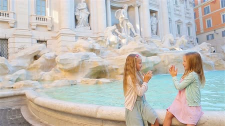 triton : Adorable little girls near the Fountain of Trevi in Rome. Happy kids enjoy their european vacation in Italy Stock Footage