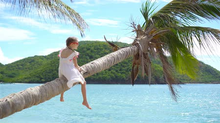 palmtree : Little girl at tropical beach sitting on palm tree and havinf a lot of fun. Kid on caribbean vacation in Antigua island