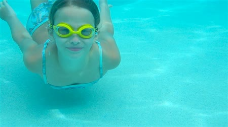 submerge : The little girl in the swimming pool underwater and smiling Stock Footage