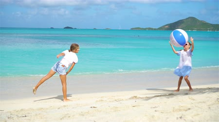 caribe : Little adorable girls playing with ball on the beach.