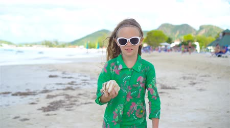 concha : Little cute girl with seashell in hands at tropical beach. Adorable little girl playing with seashells on beach