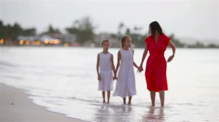 gyengéd : Adorable little girls and young mother on white beach