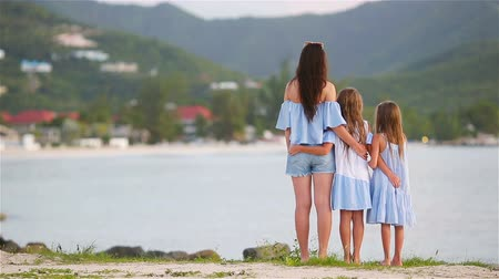tendo : Beautiful mother and her adorable little daughters on the beach Vídeos