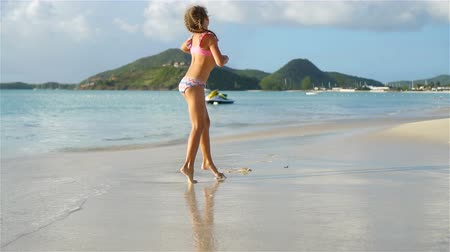 handstand : Little active girl making cartwheels on white beach.