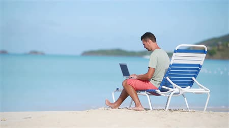 kommunikátor : Young man with laptop on tropical beach.