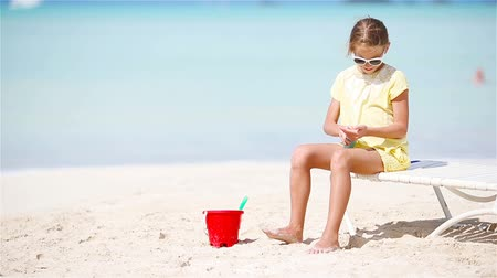 sunblock : Little girl with bottle of sun cream sitting at tropical beach Stock Footage
