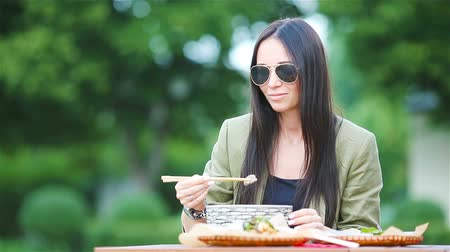 суп : Young woman eating take away noodles on the street