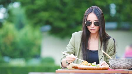 cena urbana : Young woman eating take away noodles on the street