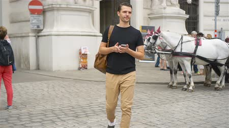 hackney carriage : Tourist man enjoying a stroll through Vienna and looking at the beautiful horses in the carriage