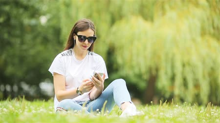 instante : Cute woman is reading text message on mobile phone while sitting in the park.
