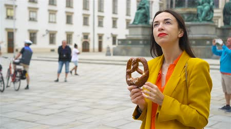 viennese : Beautiful young woman holding pretzel and relaxing in park