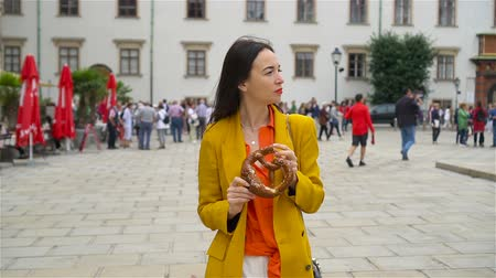 pretzel : Beautiful young woman holding pretzel and relaxing in park