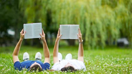 книги : Relaxed young couple reading books while lying on grass Стоковые видеозаписи