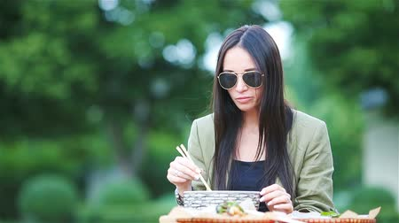 nekvalitní potraviny : Young woman eating take away noodles on the street