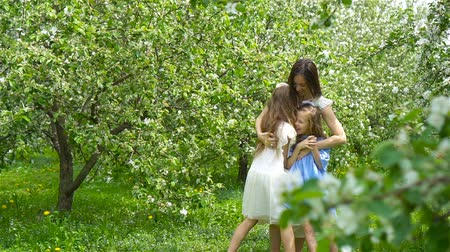 отпрыск : Adorable little girls with young mother in blooming garden on beautiful spring day having fun together
