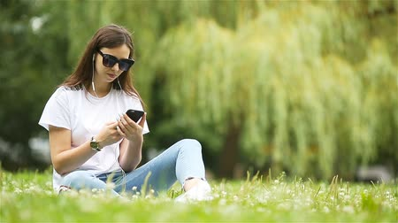 anlık : Cute woman is reading text message on mobile phone while sitting in the park.