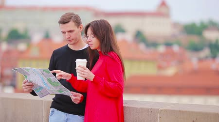 directional : Young tourist couple traveling on holidays in Europe smiling happy. Caucasian family with city map in search of attractions