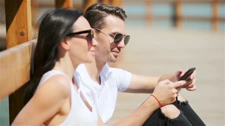 tomar : Picture of a joyful couple using smartphones in the park