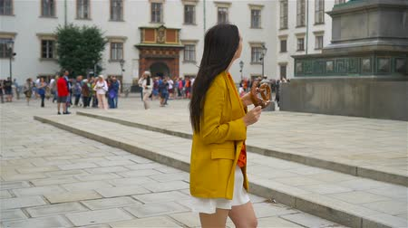 pretzel : woman eating pretzel while walking at the square Stock Footage
