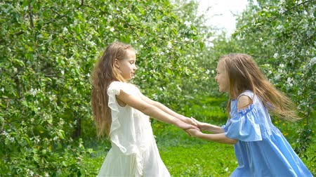 szag : Adorable little girls in blooming apple tree garden on spring day