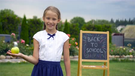 notas : Happy little schoolgirl with a chalkboard outdoor Stock Footage