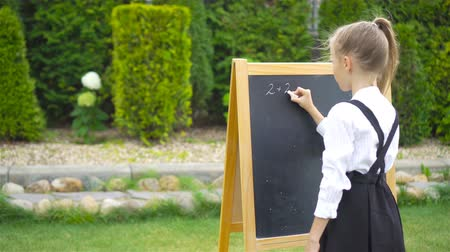 first class : Happy little schoolgirl with a chalkboard outdoor Stock Footage