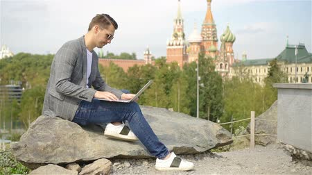 red square : Man is working by laptop while relaxing in the park