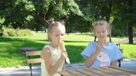язык : Little girls eating ice-cream outdoors at summer in outdoor cafe