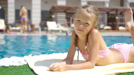 капелька : Beautiful little girl having fun near an outdoor pool