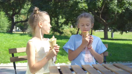 конусы : Little girls eating ice-cream  at summer