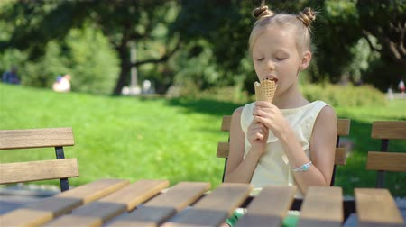 vacations cones : Little girl eating ice-cream outdoors at summer in outdoor cafe