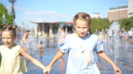 ferahlatıcı : Little adorable girls have fun in street fountain at hot sunny day