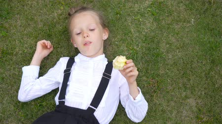 first class : Happy little schoolgirl eating apple at outdoor