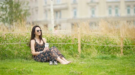 kayran : Cute woman is reading text message on mobile phone while sitting in the park.