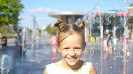 uv : Little adorable girl have fun in street fountain at hot sunny day