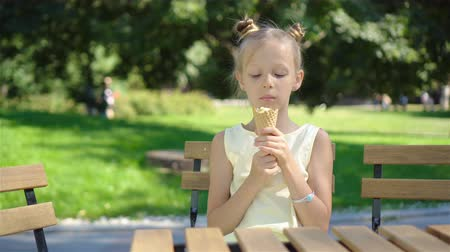 язык : Little girl eating ice-cream outdoors at summer in outdoor cafe