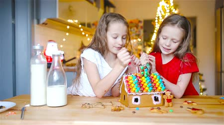 glazura : Little girls making Christmas gingerbread house at fireplace in decorated living room.