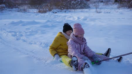trenó : Adorable little happy girls sledding in winter snowy day.