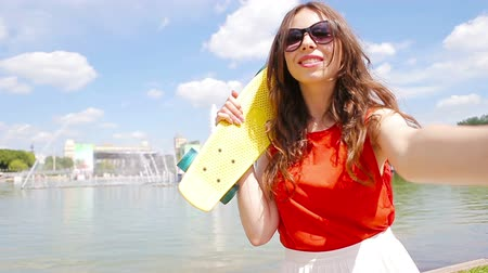 věčnost : Young girl making video selfie and having fun in the park. Lifestyle selfie portrait of young positive woman having fun and taking selfie. Concept fun with new trends and technology.