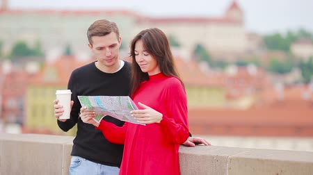 посещающий : Young tourist couple traveling on holidays in Europe smiling happy. Caucasian family with city map in search of attractions