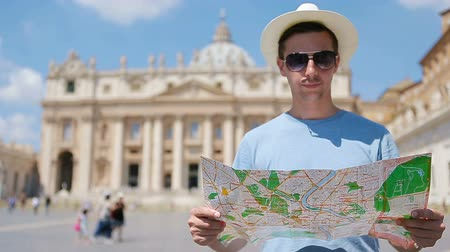 piazza : Young man with city map in Vatican city and St. Peters Basilica church, Rome, Italy. Travel tourist man with map outdoors during holidays in Europe.