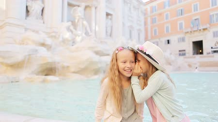 triton : Adorable little girls whispering sitting on the edge of Fountain of Trevi in Rome. Happy kids enjoy their european vacation in Italy