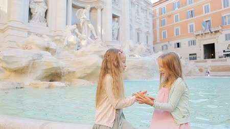 barok : Adorable little girls having fun at the Fountain of Trevi in Rome. Happy kids enjoy their european vacation in Italy Stok Video