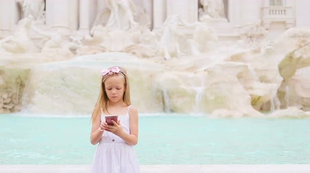 fontain : Adorable little girl with smart phone at warm day outdoors in european city near famous Fontana di Trevi