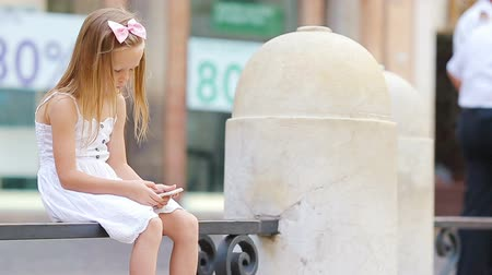 fontain : Adorable little girl with cellphone at warm day outdoors in european city near famous Fontana di Trevi